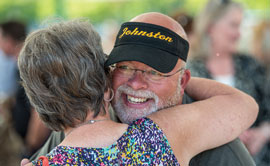 Bill Johnston gets a hug from a well-wisher at his retirement party in August, which was held at Caras Park in Missoula. More than 300 people were in attendance.
