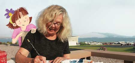 Lynne Avril illustrates on her deck in Polson as character Amelia looks on