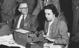 Dorothy Rochon Powers was one of the few women reporters assigned to President Dwight D. Eisenhower's dedication of McNary Dam. Busy filing a story on the president's arrival, she chats with Press Secretary James Hagerty in the press room at the Marcus Whitman Hotel in Walla Walla, Wash., in October 1954.