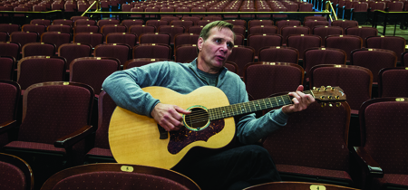 "Tim Ryan Rouillier picks his guitar while chatting inside UM's Dennison Theatre. Ryan, a country music artist in Nashville originally from tiny St. Ignatius, will debut his symphonic memoir, ""Play Me Montana,"" inside the same theater on June 17."