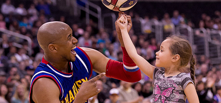 Christensen helps a young fan spin a basketball on her finger at the Staples Center in Los Angeles. (Photo by Harlem Globetrotters International, Inc.)