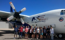 Students and researchers stand outside a plane that contains a laboratory.