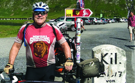 Earnie Williamson '73 dons his Griz cycling jersey atop Oberalppass in Switzerland near the source of the Rhine River.
