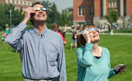 President Sheila Stearns and anthropology instructor Garry Kerr watch the solar eclipse Aug. 21 on the Oval.