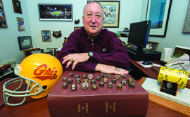 Dave Guffey has accrued quite the collection of Griz memorabilia during his career, including twenty-six championship rings perched here atop The Red Book. The two he wears are from national championships. (Photo by Todd Goodrich)