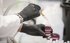 a gloved hand holding a pipette